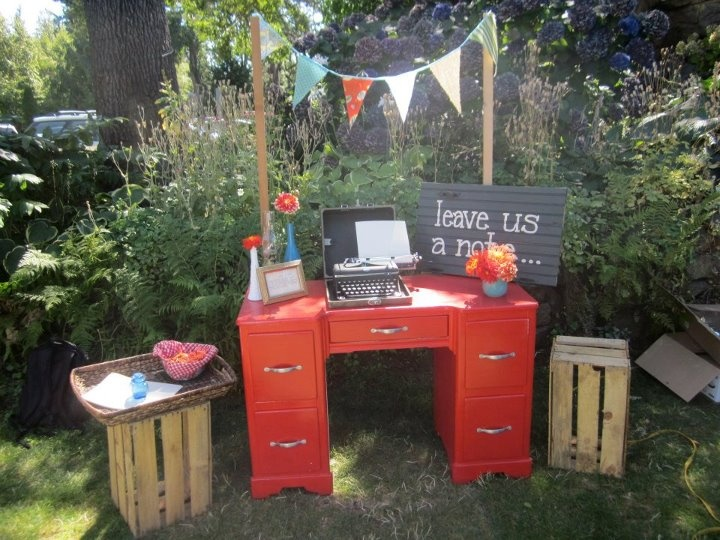 """Our old fashioned typewriter for friends to write notes, in lieu of a guestbook.  We bought the desk off craigslist, painted the """"leave us a note"""" sign on an old recycled cabinet door we found at a """"rebuild-it"""" center, and the flags were made from vintage fabric, mounted by 2 dowels in the ground behind.  The crates were free from behind a produce place-- they gave us permission to take them, and we gathered about 15 of them during the months leading up to the wedding."""