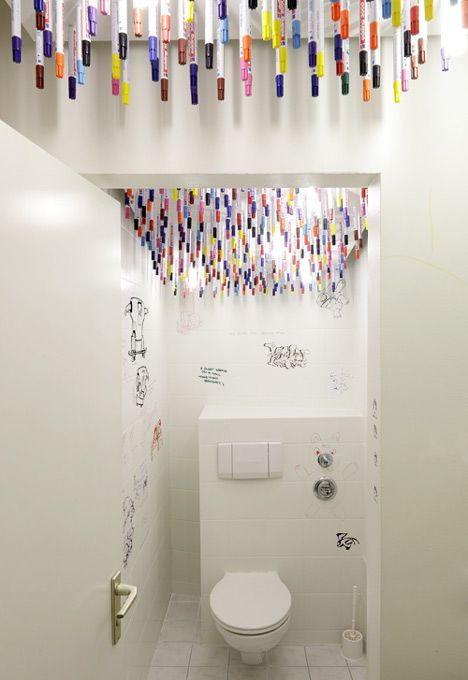 advertising agency lavatory cubicle has pens attached to the ceiling with magnets inviting users to doodle on the walls