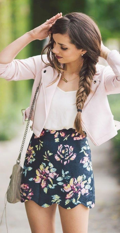 Veste en cuir rose pâle sur un top blanc, jupe noir à fleurs, sac en bandoulière, coiffure tresse