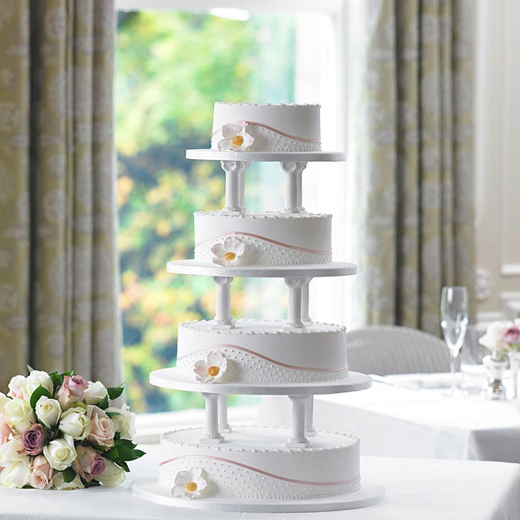 Bettys Hedgerow Rose Wedding Cake | The handmade hedgerow rose on this cake adds a gorgeous finishing touch to this unique oval-shaped design, perfectly setting off the curved panel of handpiped dots, which is delicately edged with ribbon.    Each tier is covered in royal icing, edged with handpiped scrolls and trimmed with fine beadwork for a pretty finish.