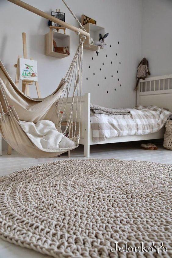 Dormitorio infantiles con tonos neutros con alfombra redonda de ganchillo