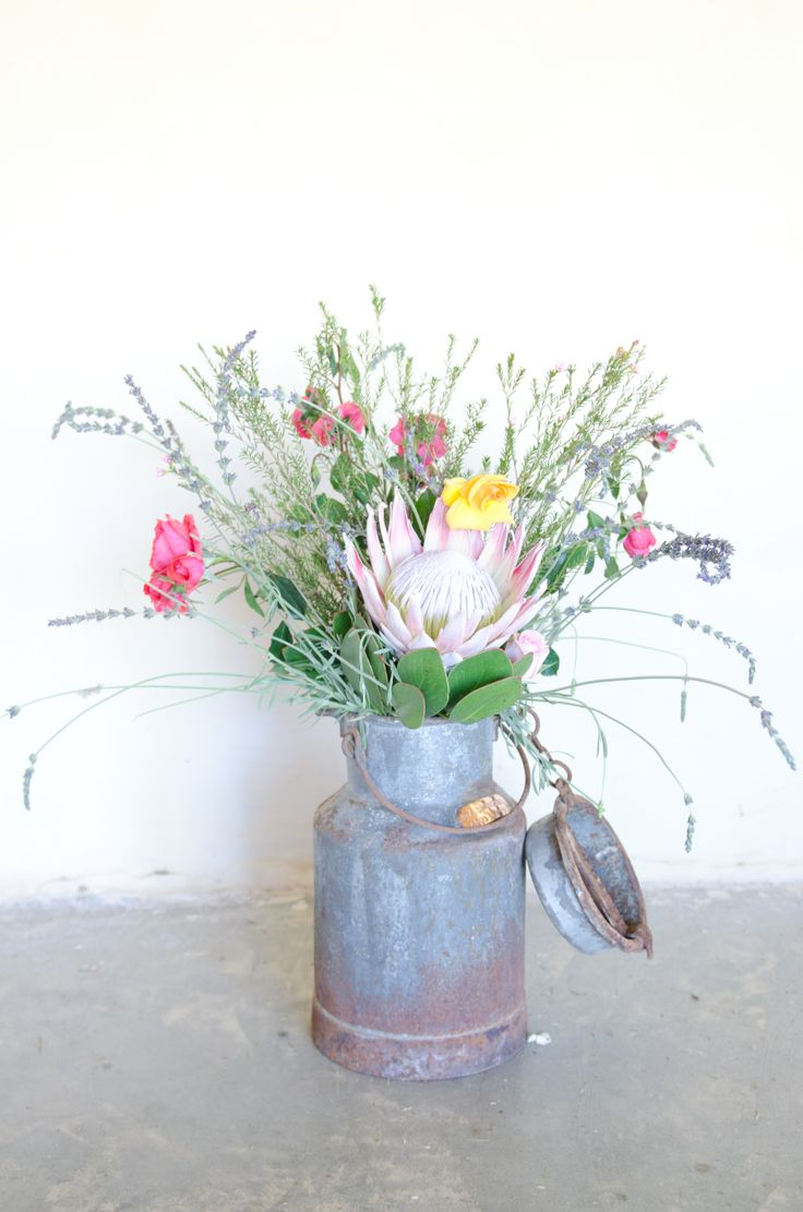 Country Flower mix with Proteas in an antique milking can