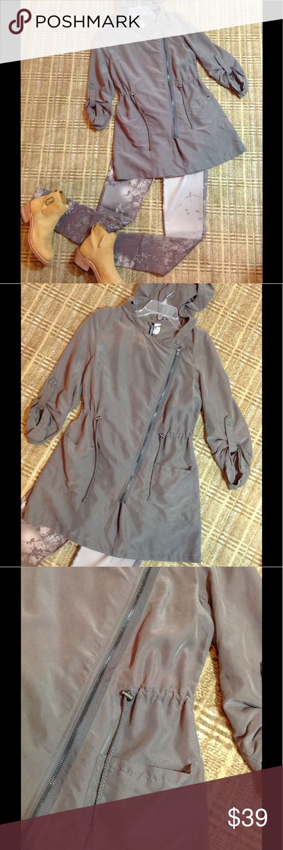 Divided by H&M Anorak Size 4 Asymmetrical zip front anorak. Silk like; model/polyester blend. Feels like silk yet machine washable. Drawstring at waist. 2 front pockets. Button up sleeves. Hood. Khaki green. Size 4. (Shown with New Buffalo David Bitton mid rise skinny pants. Tan multi 26. And Timberland booties 7) both also for sale!! Divided Jackets & Coats Utility Jackets