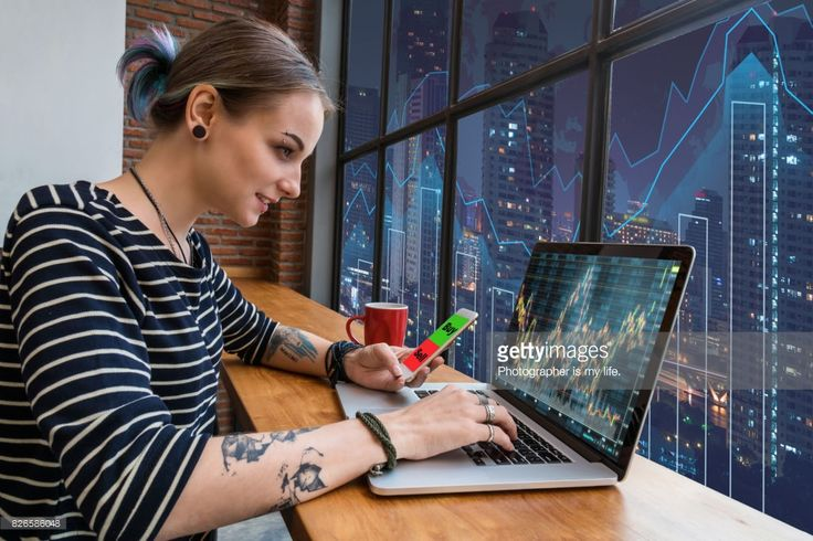 Stock Photo : Business financial and forex concept, Hipster young Woman freelancer using the technology laptop and smart phone mobile showing trading graph with the stock exchange trading graph screen background