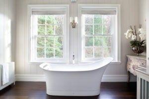 Eine Übergangszeit weißen Badezimmer mit dunklen Holzböden, freistehende Badewanne und Twin Fensterpaneele. / Foto von Paul Craig Fotografie