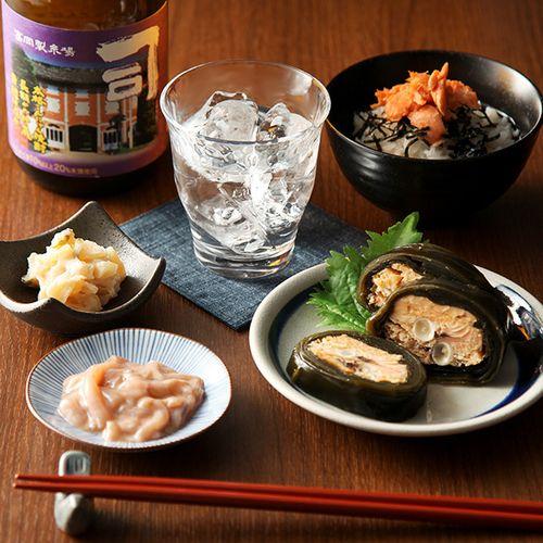 いかの赤作りは日本近海で漁獲される「するめいか」を細切りにし、いかわた(肝臓)と和え、調味・熟成させております。山海漬は大根、きゅうりを細かく刻み数の子を和え、酒粕に漬け込み辛味をきかせているのが特徴です。だし茶漬は手塩にかけて漬け込み、丁寧に焼き上げてほぐしたアラスカ産の紅鮭を使ったお酒のシメにぴったりのお茶漬けです。鮭の昆布巻はキングサーモンの中骨を昆布で巻き、醤油・みりん・清酒・だし汁などで、じっくりと煮込みました。こんにゃく焼酎は淡麗でありながらほのかな甘味も備わったクセが少なく非常に飲みやすい本格焼酎です。世界文化遺産に登録された「富岡製糸場」をラベルに使用したレトロモダンなデザインが魅力的です。