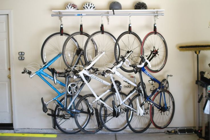 DIY Bike Rack for 90 bucks | heavy duty velcro straps, hooks/carabiners, pole, and shelf above for helmets/pads, etc.