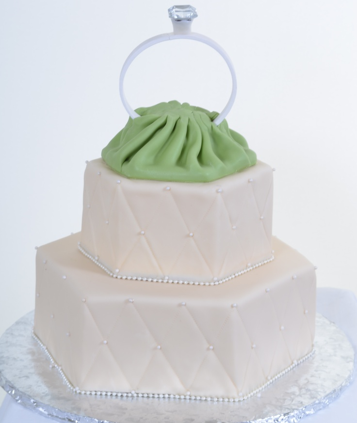 Pastry Palace Las Vegas - Wedding Cake #557 – Put A Ring On It. Two hexagon shaped, fondant-covered tiers of pearly white, with quilted faces and green 'silk' presentation of large engagement ring topper.