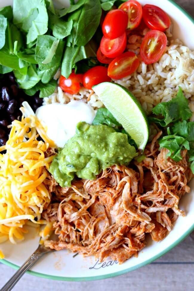 Instant Pot Savory Pork Burrito Bowls--perfectly tender and shreddable 5 ingredient pork is cooked quickly in your Instant Pot and then served with rice, guacamole, black beans, sour cream and more of your favorite toppings.