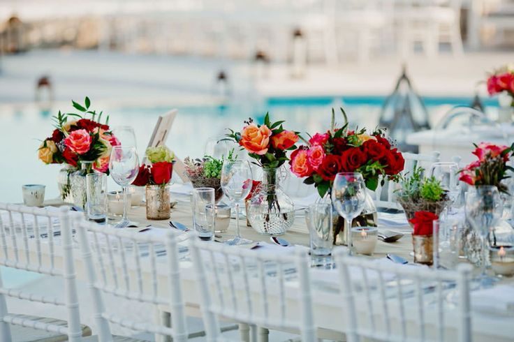 Look at the magnificent contrast of the bold flower compositions on the white tables!