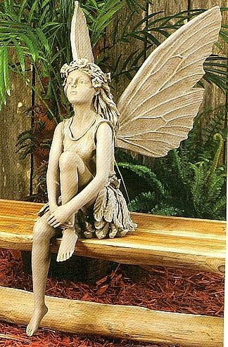Garden Statue. Cute fairy sitting on a garden bench looking up to the skies.