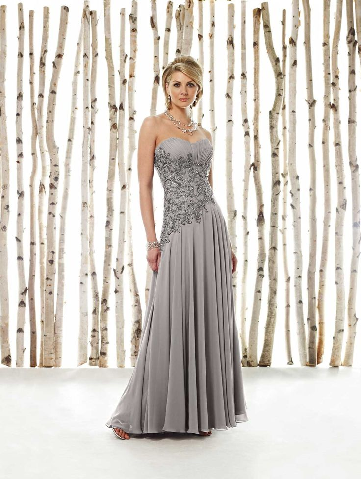 Available at Enchantment Bridal and Formal Gowns, 10 King Street West, Chatham Ontario Cameron Blake  |  Mother of the Bride Dresses  |  style #211620Strapless sweetheart chiffon A-line dress with ruched Empire bust line, intricately hand-beaded and embroidered midriff with asymmetrically dropped waistline, full bias-cut gathered skirt. Matching shawl and removable straps included.