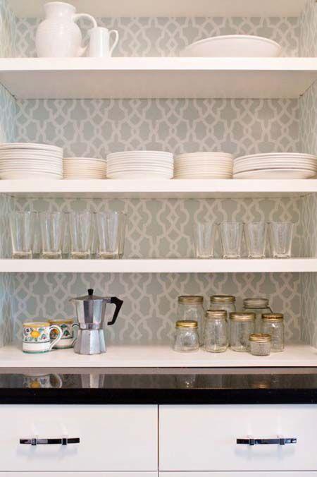 Una buena idea para la zona de baldas en tu cocina, revestir la pared con papel pintado.