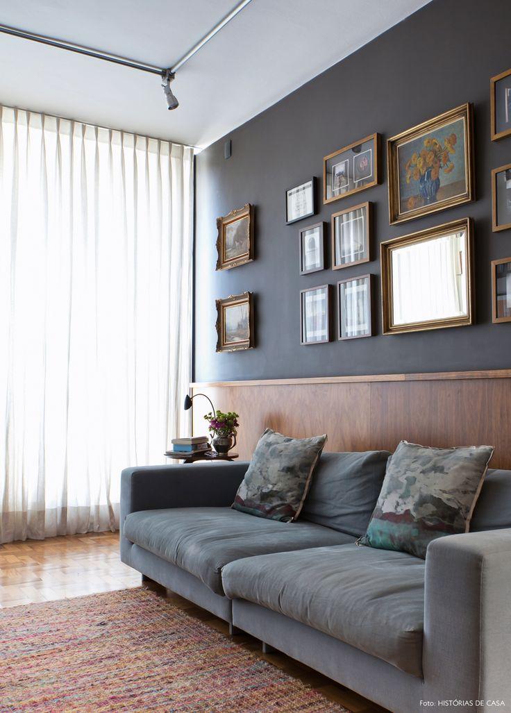 Estar tem meia parede com lambri de madeira e galeria de quadros.