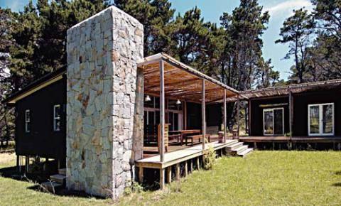 Com ares de cabana chique e moderna, a casa de 120 m² no balneário de Punta del Este, no Uruguai, se mimetiza ao bosque, quase camuflada por paredes de pínus escurecido com uma mistura de tinta preta e stain, grandes aberturas de vidro e uma generosa varanda. O volume que embute a churrasqueira é de blocos grandes de granito cinza bruto. Por fim, a idéia de erguer a morada 60 cm acima do chão foi essencial para o belo resultado, atendendo ao desejo de leveza e imersão na natureza. Projeto de…
