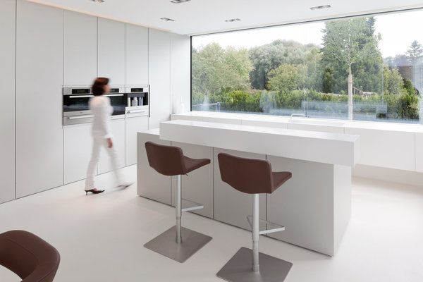 Les meubles de la cuisine avec façades de rangements,  fraisées à l'onglet, s'accompagnent d'une hotte escamotable, d'un bloc de 2,50 x 2 m et d'un plan de travail avec évier intégré fabriqué sans raccord de joint.