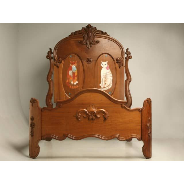 """Antique American Victorian oak bed with cat motif painted headboard. The area for the mattress measures 61"""" wide x 78""""."""