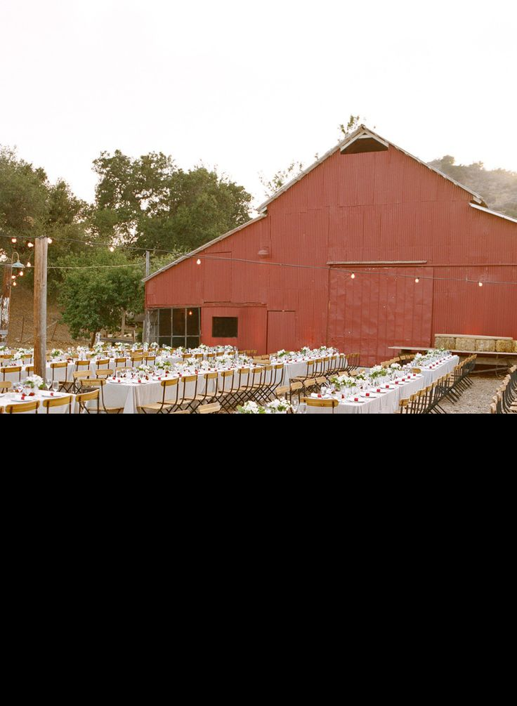 Rustic wedding reception decor with banquet style tables and a big red barn.