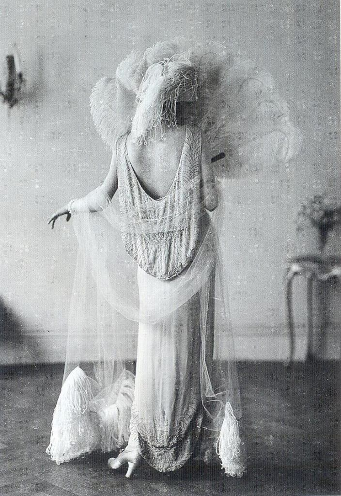 Mẫu thiết kế của Madeleine Vionnet năm 1924. Những trang phục của Madeleine Vionnet thường sử dụng rất nhiều lông vũ đính lên sản phẩm tạo nên sự quý phái cho trang phục. Mẫu thiết kế bên cũng vậy, với nhiều voan và lông vũ cùng với kiểu dáng váy suông dài tạo nên nét sang trọng cho người người mặc.