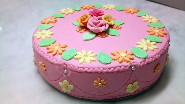 Torta decorata con fiori e roselline centrali.