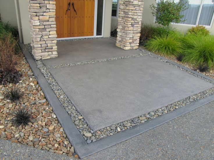 Exposed aggregate driveway, with charcoal coloured concrete inset that has been acid etched. The border is divided by loose pebbles. The outer border is also charcoal coloured concrete that has been acid etched