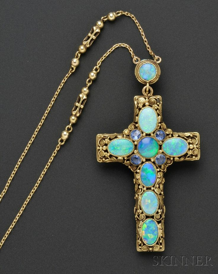 Arts & Crafts Gold, Opal, and Pearl Cross and Chain, Edward Oakes, c. 1930, set on one side with opals and circular-cut sapphires, and on the other with half pearls and onyx tablets, all among foliate motifs and scroll and gold bead accents, suspended from trace link chain with open cylinder and bead links, lg. 2 1/8, 23 1/2 in., unmarked.