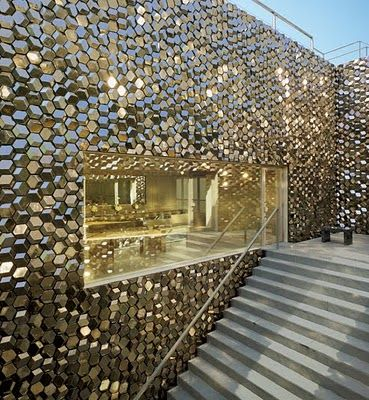 Architect Tadao Ando created an unusual guesthouse and gallery space in Tokyo for Takeo Obayashi.Walls of platinum-glazed tiles by Olafur Eliasson enclose the courtyard.