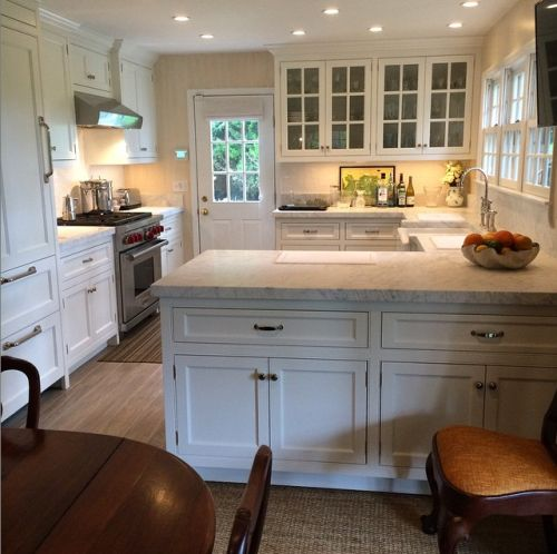 Small Southampton kitchen lives large:  Glass-fronts, large-scale hardware on paneled refrigerator, cabinetry also on dining side - Tom Samet
