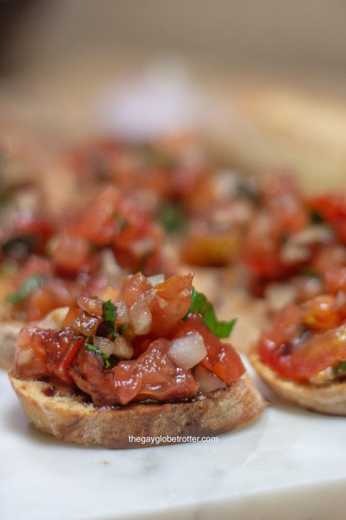 A crostini with tomatot bruschetta on a serving platter