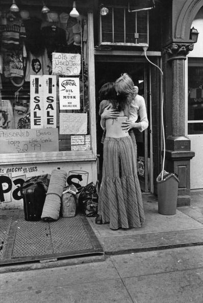 A hippie couple embrace outside a shop selling second hand clothes in St Mark's Place New York City 1972