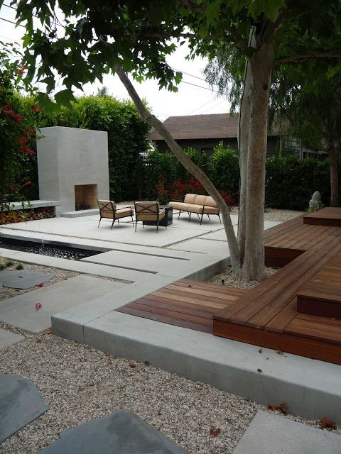 """I like that the courtyard walls are actually a hedge creating a softer feel and a """"green wall"""". Love the outdoor fireplace and modern feel. I also like the gravel with the large stone pavers."""