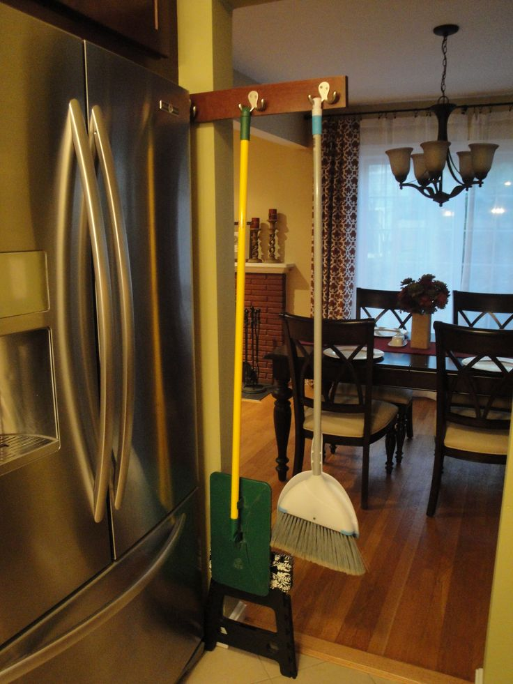 DIY sliding broom holder fits in narrow space next to fridge. Made with a drawer track, wood leftover from cabinets, and hooks.
