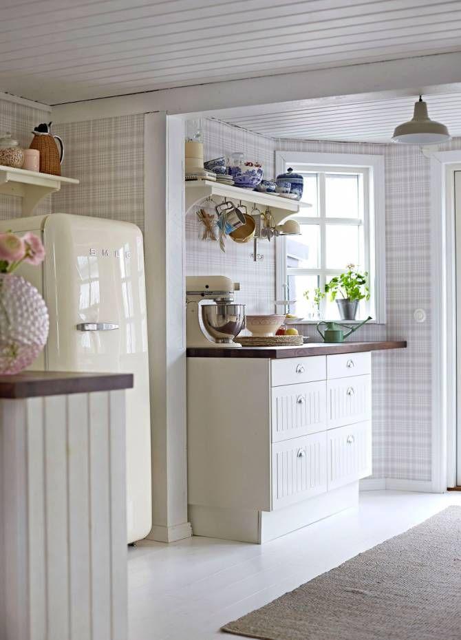 Det ljusa köket har en lantlig känsla med tapeten Rutan, Sandbergs. På hyllan står ljuvt blåvitt porslin från Royal Copenhagen. Köksskåp, Ikea, och kylskåp, Smeg.