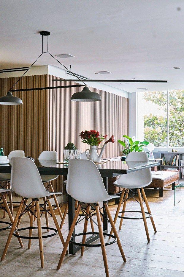 Cozinha integrada com sala de estar e mesa de jantar, decoração com tons de madeira, concreto, branco, rosa e azul claro. Reforma de apartamento estilo Retrofit. Na mesa de jantar preta, banquetas Eames na cor branca. Em uma das paredes revestimento com ripas de madeira, na outra parede com tijolo aparente pintados de branco, piso de taco com mix de cerâmica cinza. Decoração de Apartamento em Higienópolis, São Paulo