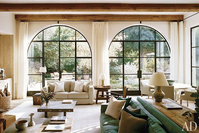High ceilings with rustic wood columns, arched windows framing french doors, great natural light