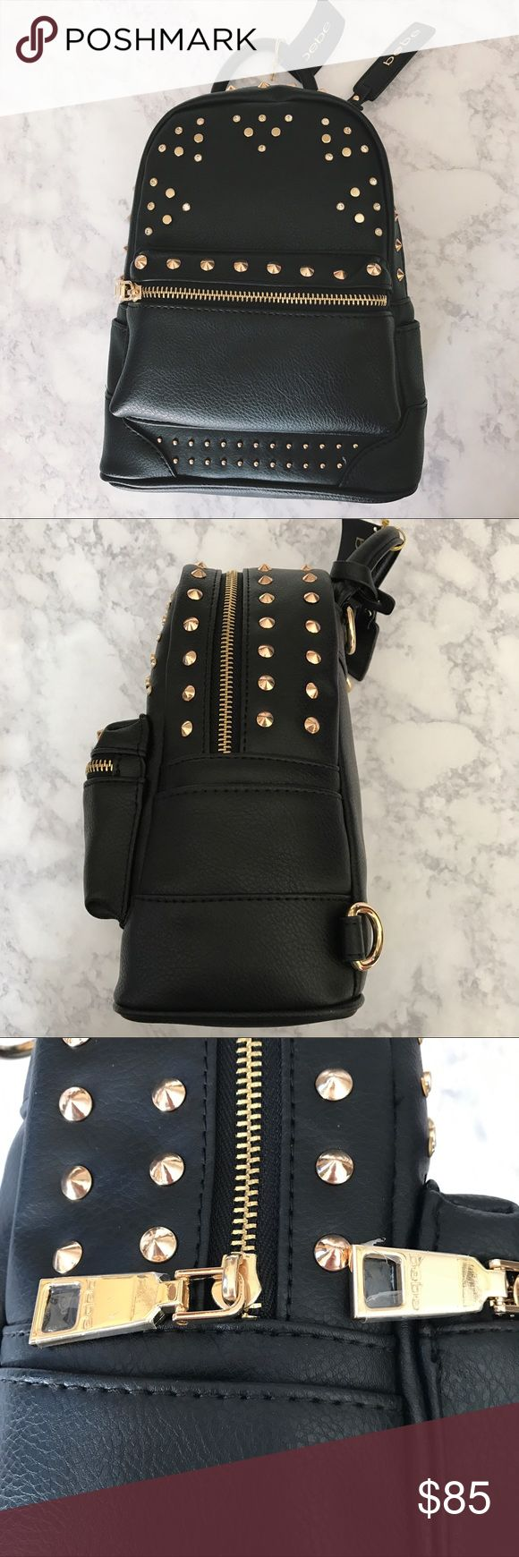 """Bebe Mini Studded Backpack Brand new. Never used. Decorated with studs. Straps haven't been attached yet- still wrapped. Zippers still have protective film. One zippered pocket on front. One small slip pocket on both left and right side. Main compartment has a large slip pocket inside. Measures approximately 10"""" in height, 7 & 1/2"""" in width, and 4"""" in depth. Comes from a smoke free and pet friendly home. bebe Bags Backpacks"""