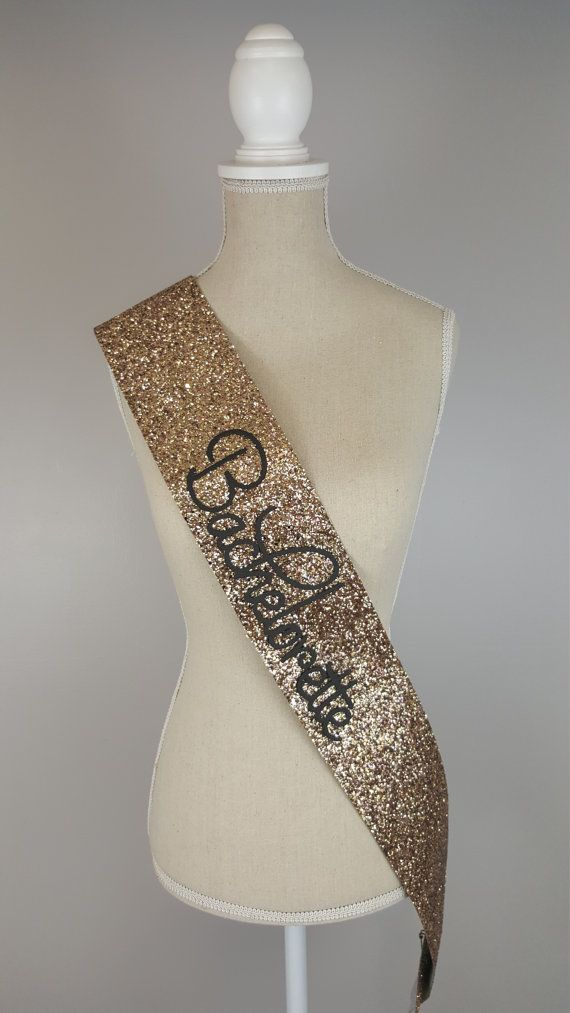 Beautiful handmade gold glitter Bachelorette sash. Gold Bachelorette sash comes with black text. Perfect for hen party or bachelorette party / bridal shower. There are colour choices for this product; gold, silver, black and pink Please have a look at out other listings for colours. This product can be personalised - have a look at our shop listings. Please note - These are handmade made from a heavy glitter material and may vary in shape/ size. Check out our Instagram page for a short vi...