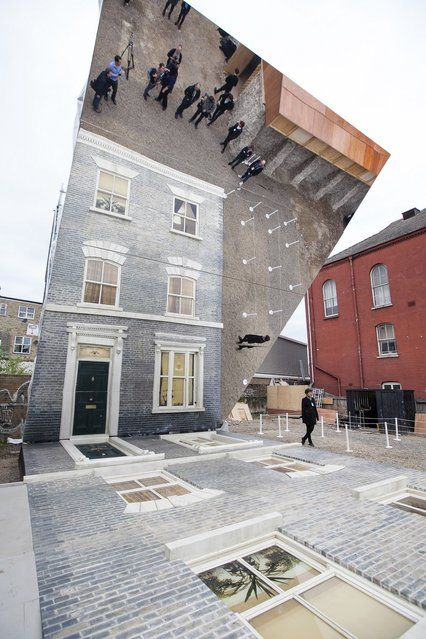 """Men appear in a window as a large-scale installation art piece by Leandro Erlich, named """"Dalston House"""", is displayed on June 24, 2013 in London, England. Part of the """"Beyond Barbican"""" summer series of events, the interactive installation is a full facade of a late nineteenth-century  http://avaxnews.me/appealing/Leandro_Erlich_Creates_a_House_of_Mirrors.html"""
