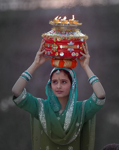 This woman is carrying a traditional Hindu vase on top of her head. This is a religious ritual that is incorporated with the beliefs of the Hindu religion.