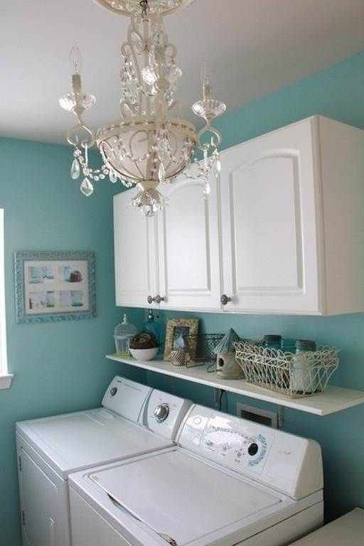 Laundry Room with shelves under cabinets....and beautiful chandelier! I would lower the shelf to just touch the top of the machines, so nothing could fall down in there.  But the chandelier... so fun. Love the blue too!