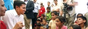 USAID Administrator Shah listening to children in a Syrian refugee camp in Jordan (AP Images)
