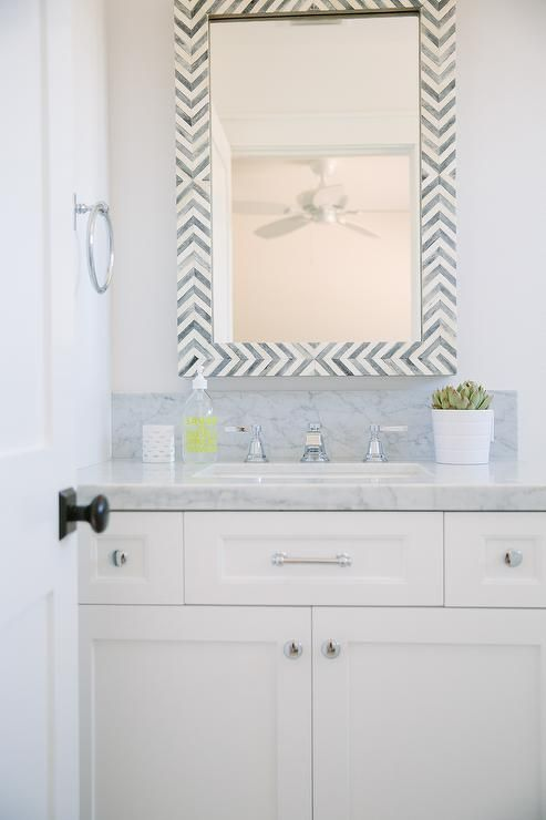 White and gray bathroom features a West Elm Parsons Wall Mirror - Gray Herringbone placed above a white shaker vanity topped with carrera marble.