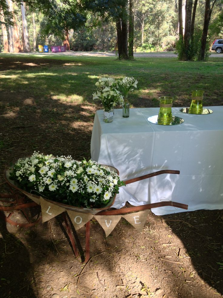 Old metal wheelbarrow full of fresh flowers - gyp chrysanthemum alsromeria & lillys all in white. The empty green vases are for the bride, bridesmaids & flowergirls bouquets to sit in after the ceremony & photos etc.