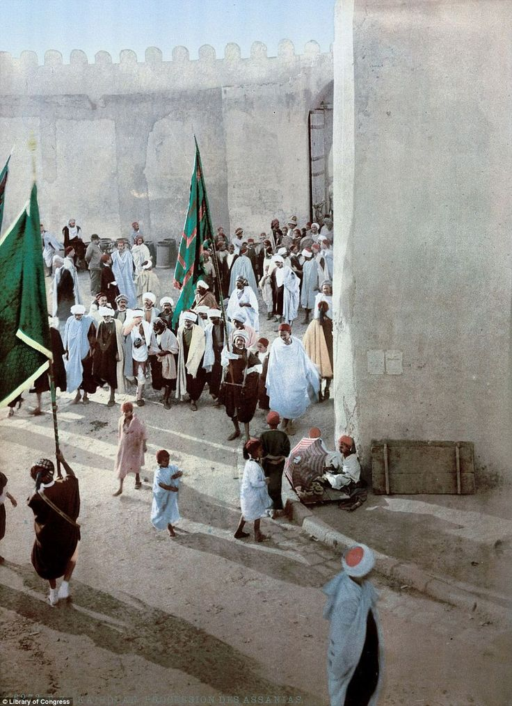 A procession, with men holding large flags, goes through the centre of Kairwan, in the north of Tunisia in 1899