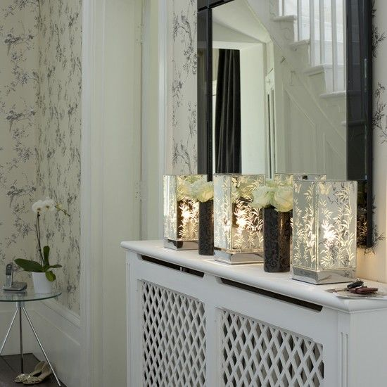 This hallway uses feature lights to create a welcoming feel. A row of mirrored lights is the perfect choice for narrow spaces like hallways and form a pretty display. A large mirror adds the illusion of more space.