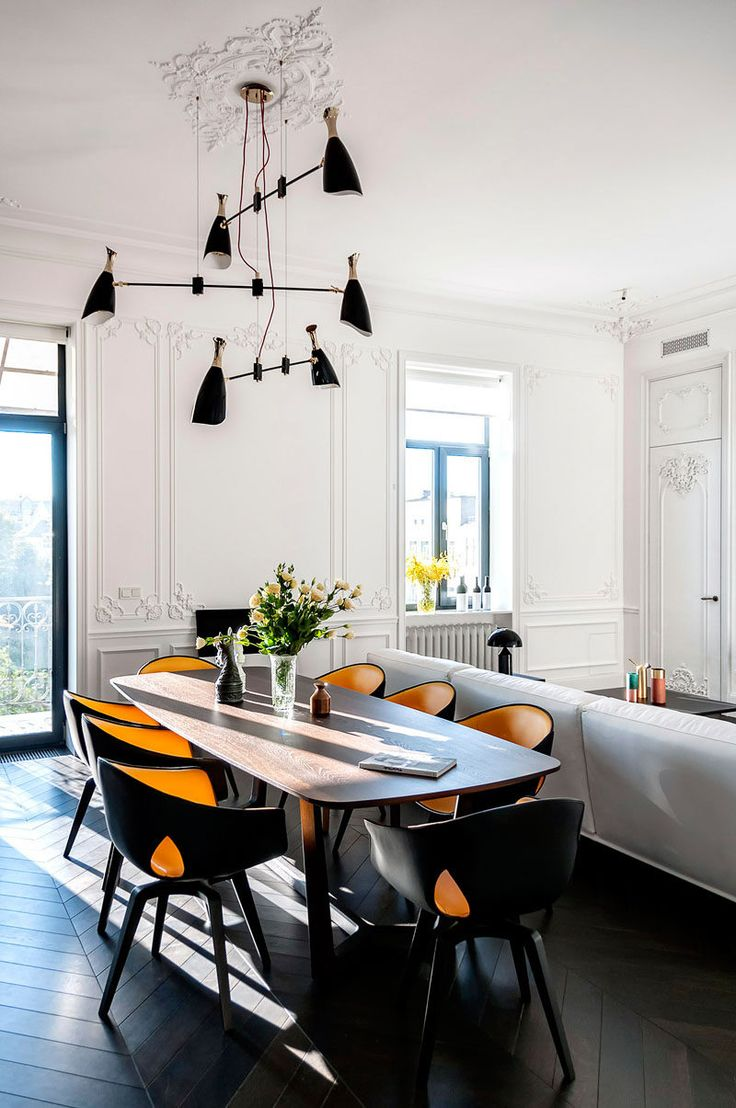 In the main living area of this apartment, the space feels large with the tall bright white walls and high ceiling. The classic wall designs contrast with the modern furniture and dark floors. A sculptural pendant light anchors the dining table in the space.