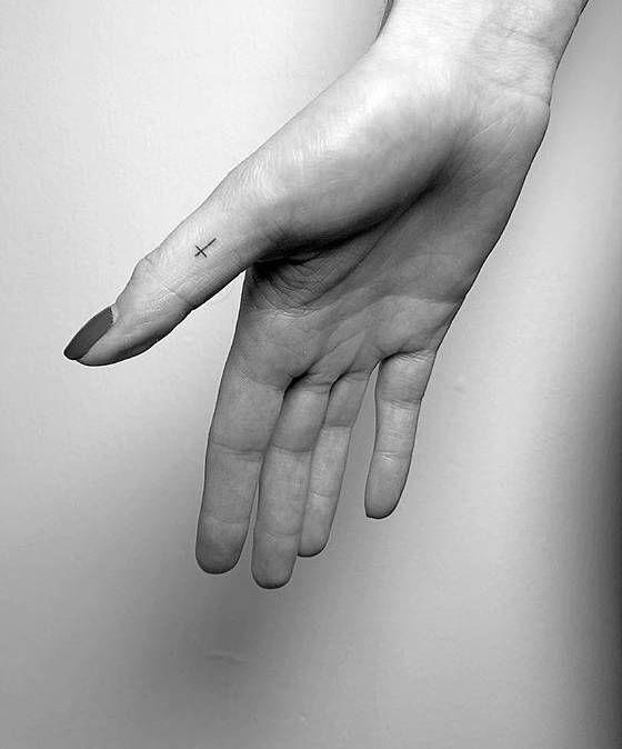Tiny cross tattoo on the thumb.