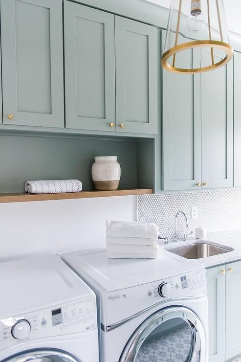 Exquisitely designed green gray laundry room is lit by a brass and glass lantern hung in front of green gray shaker cabinets accented with brass knobs and a wood shelf fixed above a white front loading washer and dryer.