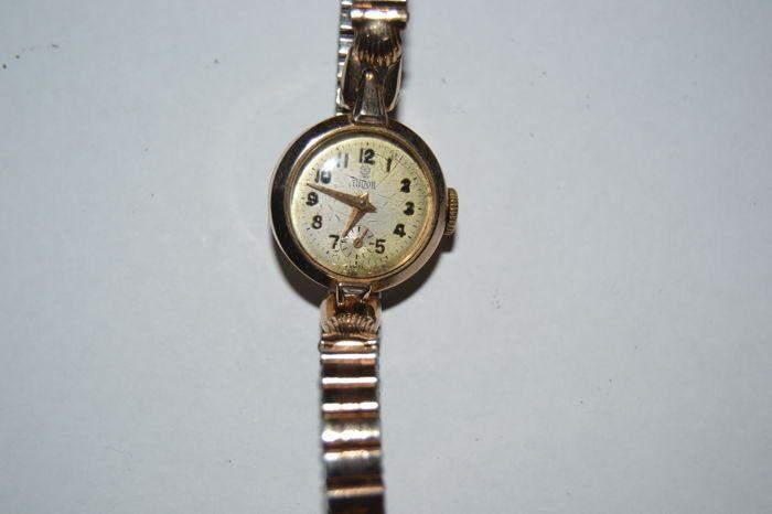 Tudor women's watch - jaren 1940/jaren 1950  Een mooie Rolex gemaakt onder de merknaam Tudor - jaren 1940/jaren 1950.De Tudor is een sub-merk van Rolex waarmee Swiss made ETA in plaats van Rolex bewegingen.De beweging is in een 9 kt massief gouden Handley behuizing.De massief gouden behuizing en het kristal zijn in uitstekende conditie terwijl de wijzerplaat is licht verkleurd.Case diameter: 2 cm - lengte van de riem (zonder kiezen): 16 cm.Het verkeer lijkt schoon maar het horloge is niet in…