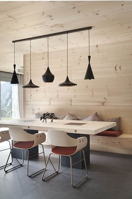 wooden dining area with Tom Dixon Beat Brass lamps